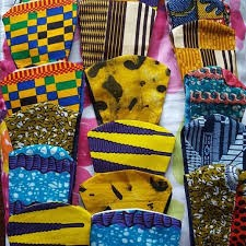 photograph of pile of colorful mask in African textiles