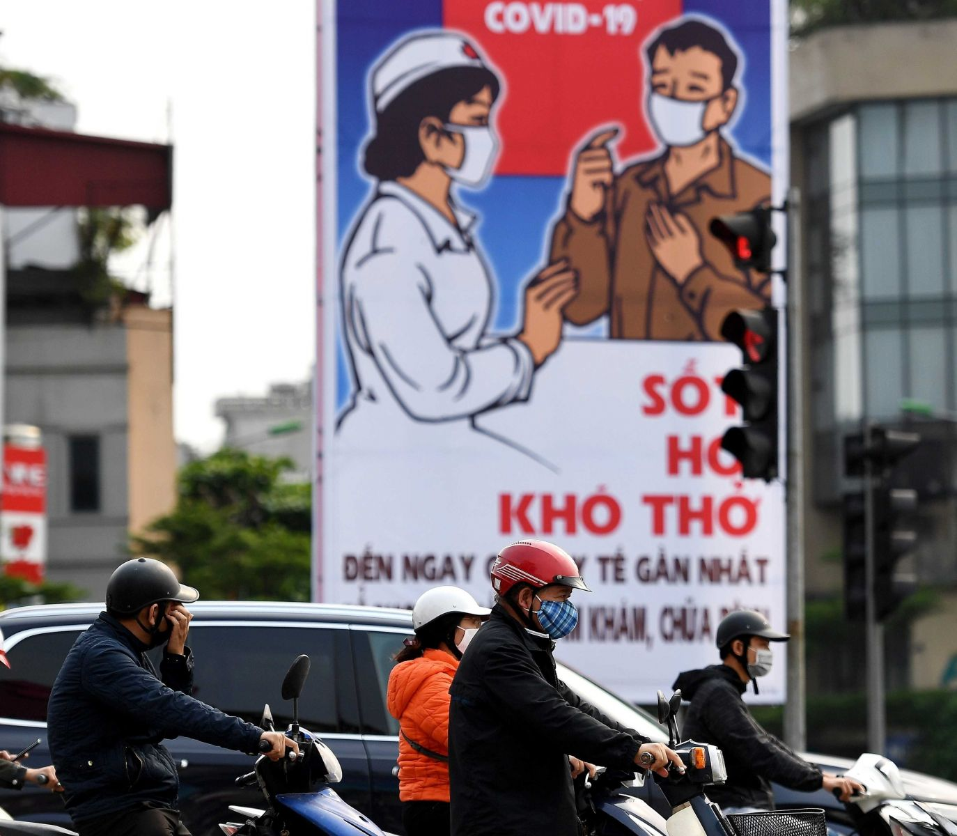 motorcycles on busy Hanoi street passing by billboard uging masks to prevent against Covid-19
